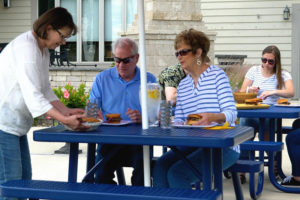 Adults sitting at a blue 4' perforated picnic table